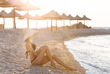 woman in black swimsuit lays on the sand. Summer vacation