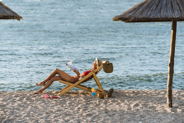 A girl with exotic cocktail tanning on the beach