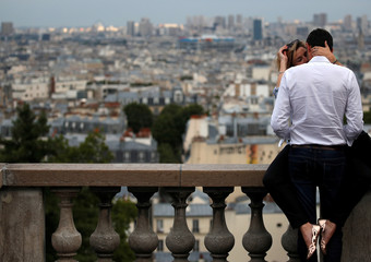 A couple is seen kissing on a sightseeing point overlooking Paris