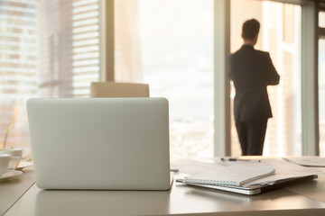 Back view of workplace, focus on office desk with laptops and documents, male silhouette at background, successful businessman standing near window, having a break at work after meeting