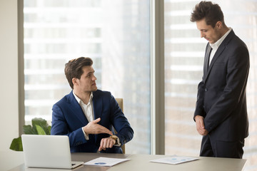 Male subordinate receiving reprimand from boss for being too late at meeting, company director scolding unpunctual manager for missing deadline or not finishing work on time, pointing on wristwatch