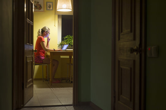 Woman working with laptop computer at night. Remote work. Work at home.