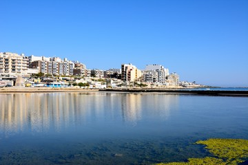 View of salt pans with buildings to the rear in Salina Bay, Bugibba, Malta.