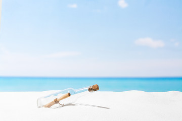 Message in bottle on beach with white sand,  in tropical sea