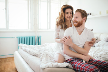 Beautiful happy couple waking up smiling in bedroom