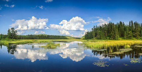 Blue mirror lake reflections of clouds and landscape. Ontario, Canada.