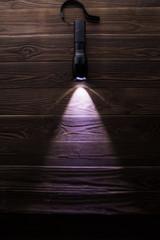 Included flashlight on wooden texture