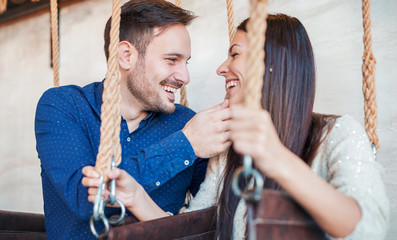 Handsome loving couple relaxing in swing while talking and flirting. Love and tenderness, romance, dating, relationships