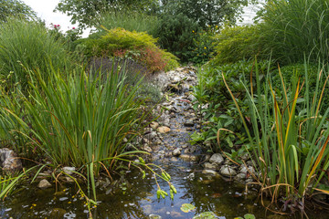 Custom made river flowing to a garden pond.