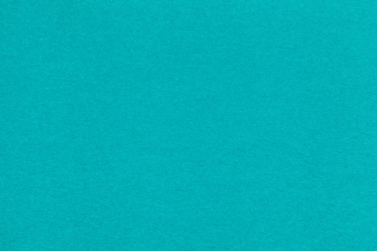 Texture of old turquoise paper closeup. Structure of a dense cardboard. The blue background.