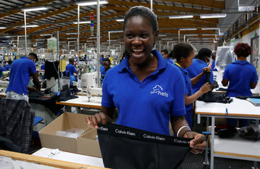 A Kenyan worker laughs as she packs men's underwear at the Hela intimates export processing zone limited factory in Athi River, near Nairobi