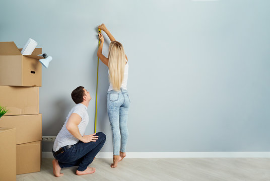 A young couple measures a tape measure on a wall in a new apartment.