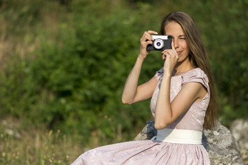 Beautiful woman is taking picture with old fashioned camera, outdoors.