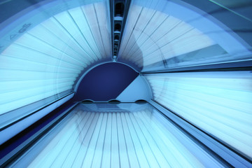 Solarium empty tanning bed in modern beauty salon, view from inside with closed lid and all light bulbs glowing on. Concept of sunbath, beauty lifestyle and healthcare