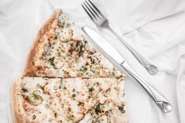 Pieces of pizza on a plate, fork and knife on a white tablecloth