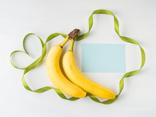 Two bananas with green ribbon frame and heart symbol on white background