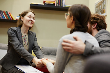 Portrait of smiling female psychiatrist holding clients hands heartily congratulating on progress in couples counseling