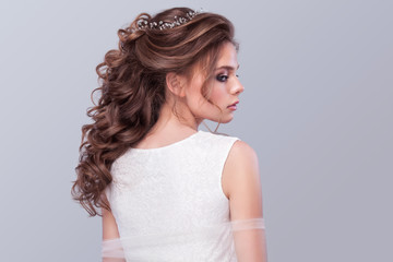 Beautiful bride with fashion wedding hairstyle - on gray background. Closeup portrait of young gorgeous bride. Wedding. Studio shot with copy space.