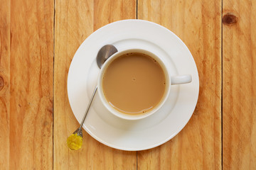 Coffee cup with spoon on wooden table, Top view.