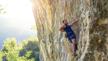 Rock climber bouldering outdoors on mountain in nature