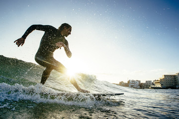 Surfer riding small wave in sea