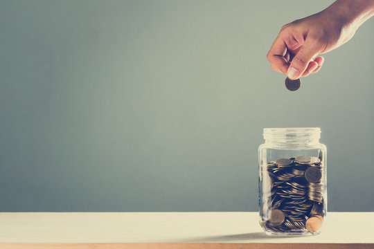 hand drops money into a glass bottle ,savings concept