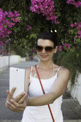 Young attractive woman in sunglasses taking selfie over beautiful bougainvillea blossom background