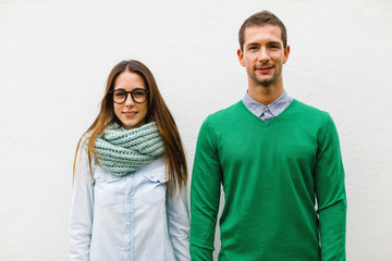 Portrait of young beautiful couple standing on white background.