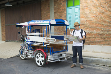 Asian man traveler is using local map while traveling in South East Asia with vintage taxi bike style.