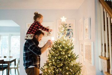 Father and daughter decorate a Christmas tree