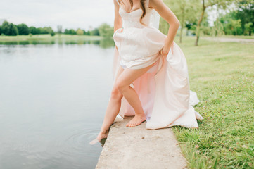Unrecognizable bride in expensive stylish wedding dress pushing her slim naked beautiful leg in river. Odd woman playing with water outdoor. Summer sunny warm day.  Unknown girl refelcted in lake.