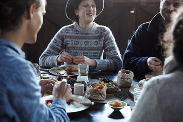Group of friends having a rustic farm to table picnic in wood barn