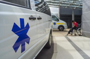 Ambulance avec étoile de vie devant un hopital et personne en  fauteuil roulante – Krankenwagen mit Star of life vor Krankenhaus und Person im Rollstuhl