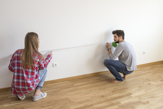 Young couple in empty flat measure wall