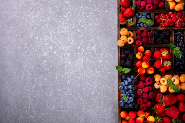 Various fresh summer Berries on the Gray Background. Mix in vintage wooden box.Food or Healthy diet concept.Super Food.Vegetarian.Top View.Copy space for Text.selective focus.