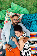 A hipster African American couple laying on blankets in the park embracing one another