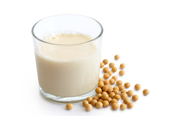 Glass of soya milk with froth isolated on white. Spilled soya beans.