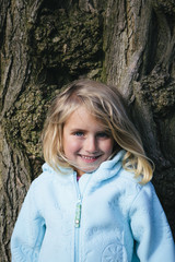 Portrait of happy four year old girl outdoors, standing in front of large elm tree