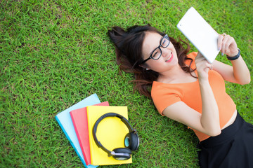 Girl laying on the grass and using the tablet, Education concept, Technology concept