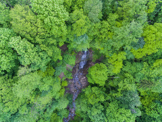 Hidden in the forest waterfall. Aerial top view.
