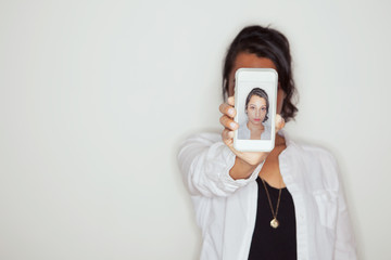 Portraits: Woman Holds Out Cel Phone With Her Image