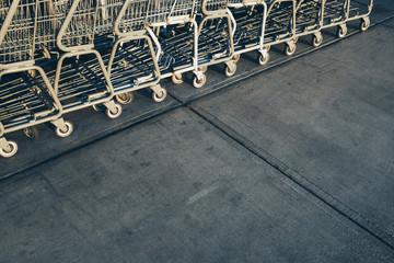 Metal grocery carts lined up on sidewalk outside supermarket