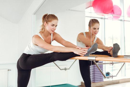 Beautiful slender woman in sportswear stretching near the ballet barre.