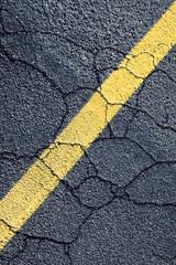 Painted yellow stripe on urban street, close up