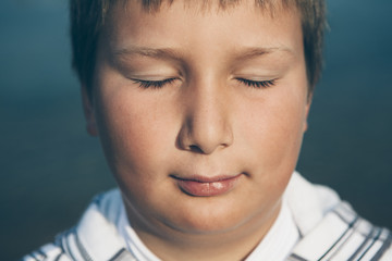 Portrait of ten year old boy with eyes closed, close up