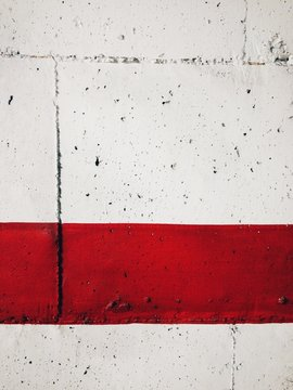 Red stripe painted on a white wall.
