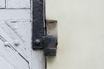 Vintage door hinge, old white wooden painted door