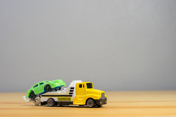 Loading broken toy car on a service tow truck on a roadside after accident on grey background.copy space