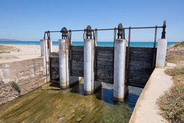 ancient sluices in waterway river towards Mediterranean Sea, next to Gurugu Beach in Castellon, Valencia, Spain, Europe. Blue clear sky