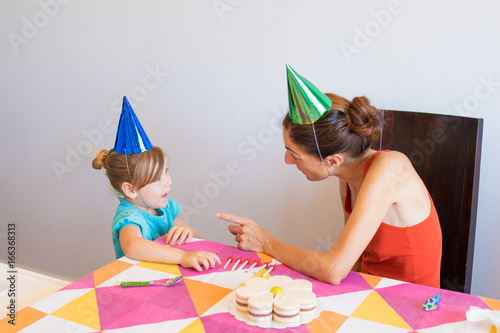 Woman With Orange Sleeveless Top Talking To Three Years Old Blonde Child Blue Shirt At